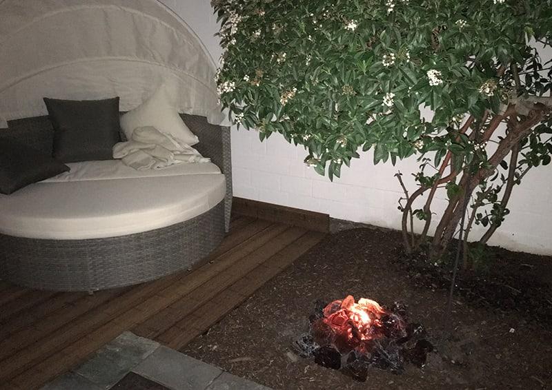 Kleiner Garten mit Lagerfeuerstelle, Baum und gemütlichem Sofa